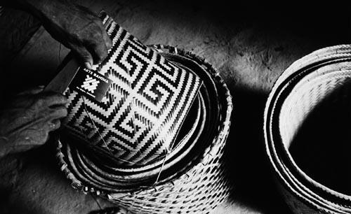 """Índio Baniwa do alto Içana (Amazonas) coloca etiqueta com a logomarca """"arte baniwa"""" num urutu de arumã, cestaria que é comercializada em São Paulo."""